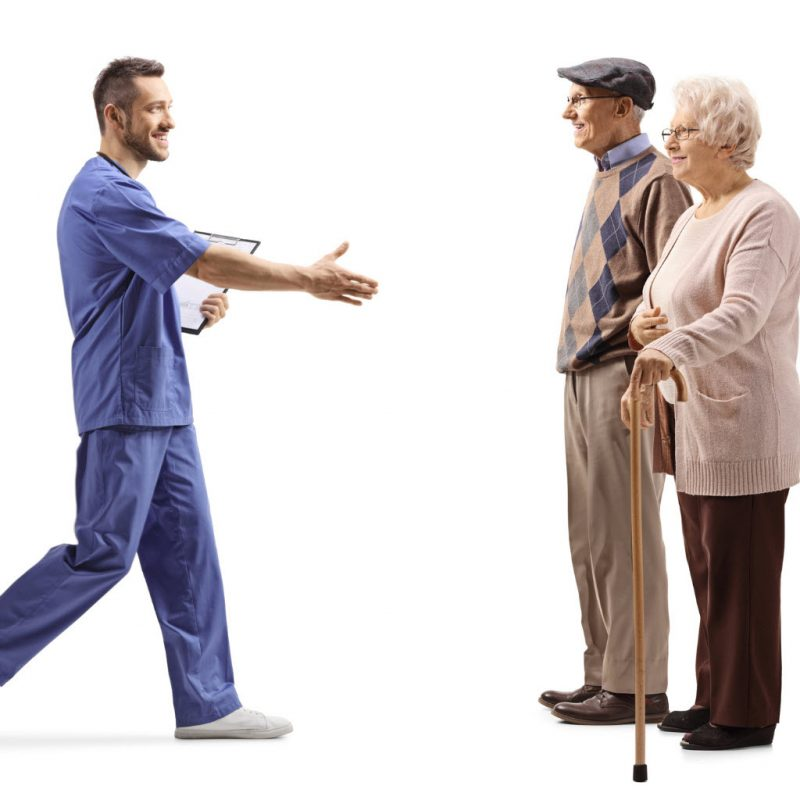 male-health-worker-walking-and-greeting-elderly-patients-with-hand